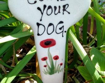 Curb your dog. Garden marker.