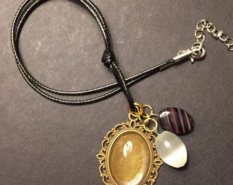 Vintage faded gold pendant with glass white and black bead accents, cord necklace