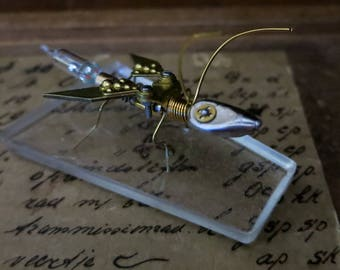 Mechanical insect desk ornament, steampunk assemblage art, miniature flying insect, vintage watch gears sculpture, biomech wasp robot.