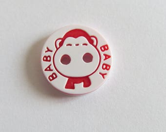 White round button with pattern of red monkey and inscription BaBy