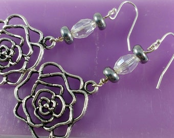 Delicate Patina Rose Accented With a Glass Bead In These Drop Earrings