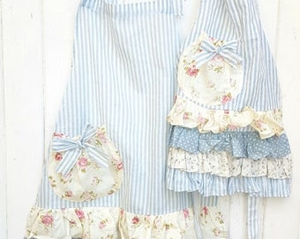 Very pretty Mommy and Me set of aprons in blue stripe with pretty floral ruffles. Mommy and me apron set. Ruffled hostess aprons.