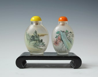 2 vintage glass snuff bottles with inside painting of flowers and landscape scene