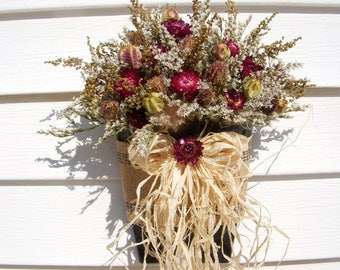Rustic vintage style wall sconce with dried herbs and flowers and a raffia bow.