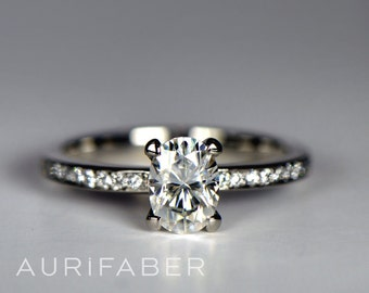 White gold oval diamond ring with total of nineteen diamonds. GIA certified oval diamond engagement ring with 0.7 carat diamond.