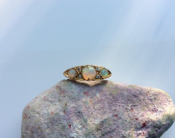 Early 20th Century opal and diamond ring, the three  opals showing the full spectrum of colours, in lovely scroll decorated 18ct gold mount