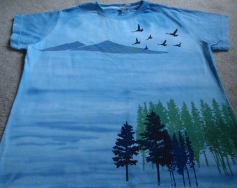 Scenic landscape setting that includes mountains, pine and fir trees, the ocean and flying birds, woman's XL screen printed and dyed t-shirt