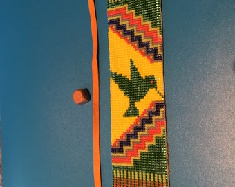Hummingbird loom beaded with Green, yellow, orange and purple beads.  Native American Inspired Bracelet with Leather Back and tie closure.