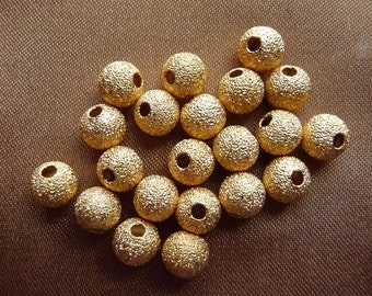 Bead, gold plated brass, 6mm, stardust, round, with 1.7mm hole, Pack Of 12 beads.