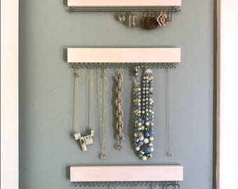 Set of three white (with gold/brass or silver/nickel) display racks: two for necklaces and bracelets, one for earrings (wall hanging)