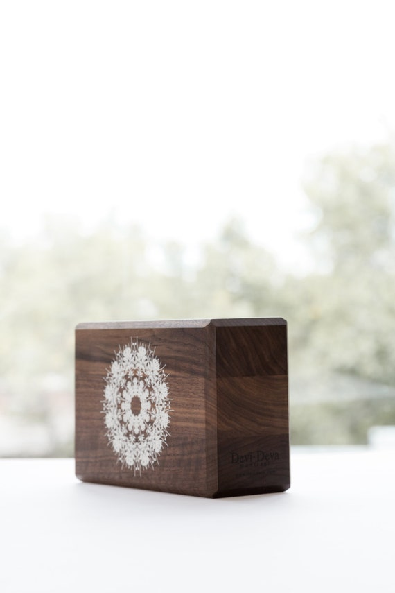 Yoga block hand made from walnut. The print is white representing a mandala. All the blocks are cover whit 3 layers of water varnish. 6DvNdI7