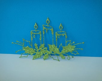 Cut out of 3 candles on glittery green Holly leaves
