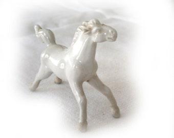 Miniature porcelain horse figurine.