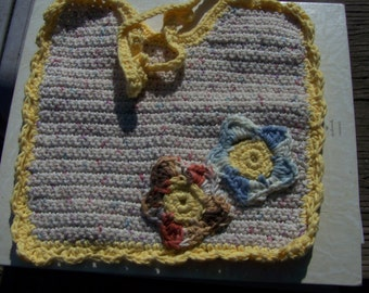 Crocheted  cotton baby bib large trimmed in yellow with decorative flowers