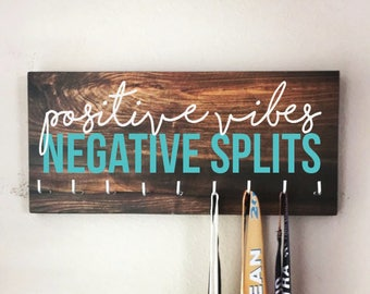 """Race Medal Holder - """"Positive VIBES, Negative SPLITS"""" white and teal with wood grain background - 16"""" wide"""