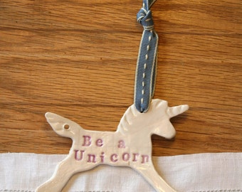 Be a Unicorn Pottery Ornament, with white and lilac glazes. Handmade pottery sent in a lovely gossamer bag ready to be given as a gift.