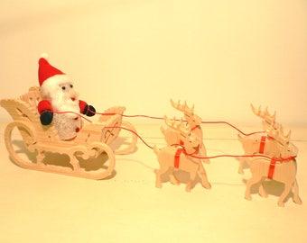 Sleigh Santa with his reindeer in woodcut