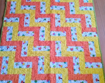 Cheerful bright baby quilt with dragon flies quilted on it