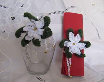 Christmas flowers, white poinsettia, a tie around bottles or napkins