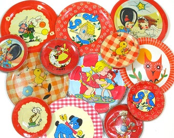 13 Tin Toy tea saucers in reds, 1950s-1960s graphics, Instant Collection.