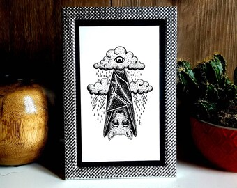 "Small frame metal, to ask, and the reproduction of an illustration ""My Bat Hates Rain"" made with ink and pen, drawing bat"