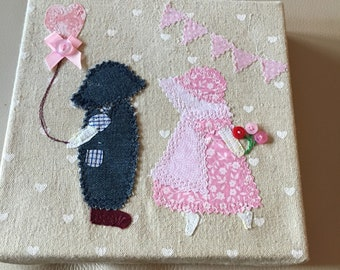 Canvas of material applique boy girl picture.