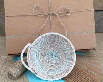 small coiled rope basket with one handle teal and orange