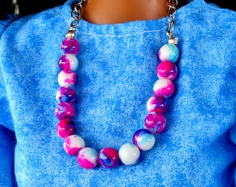 Barbie is showing off her new red,white and blue glass necklace set.