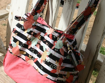 large rectangle diaper bag with black stripe with flowers with coral cotton bottom with two side pockets