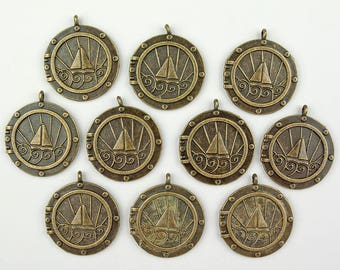 Steampunk pendants in antique brass, 10 pcs, sea theme, boat on water through porthole with sunset or sunrise, 1 inch round.