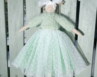 This handmade doll is perfect for spring with its frothy skirt and green jumper