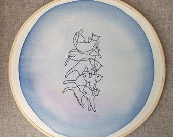 Cat embroidery that falls on his paws on a background of watercolor