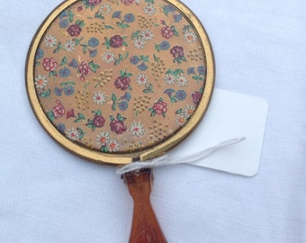 Vintage compact mirror. Gold metal handbag mirror with flower painted decoration and stand.