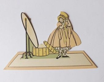 Vintage place card little girl dressing up in front of mirror with pink dress and yellow bonnet ephemera