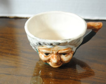 Tea Cup/ Coffee Mug with Bas Relief Face of a Old Woman on it about 2 inches tall and about 2 1/2 in dia