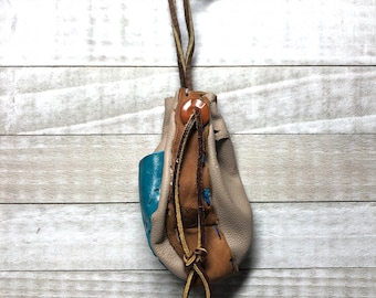 Recycled leather Ren Faire Trinket pouch with an Orange Button and a teal Contrast side
