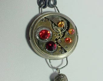 Steampunk pendant, +chain-pompon  and a vintage wrist watch case and mechanism, red and orange Swarovski crystal cabs On  black leather band