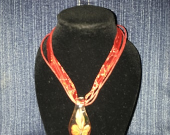 Orange flower glass teardrop pendant on a red ribbon cord necklace