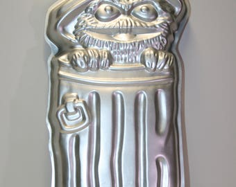 Wilton cake pan:  Oscar the Grouch; Sesame Street; 1971; copyright The Muppets Inc.