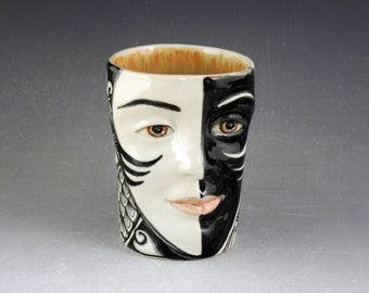 Black and white story cup, face mug, with bird, eye, topless lady and the word Imagine