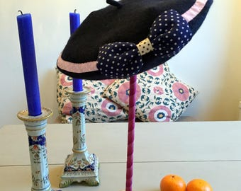 A navy blue, wool beret with a blue, polka dot bow