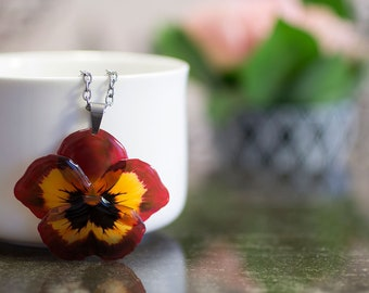 Pansy necklace on steel. Comes in a gift box. Dark red and orange flower necklace