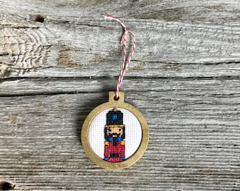 Cross stitch Nutcracker Christmas ornament in laser cut wood hoop frame for Christmas tree or holiday decor, handmade by Canadian Stitchery