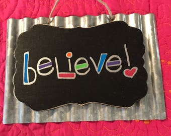 Believe metal and wood sign