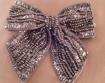 Bow to hang decorated with gray hand sewn beads