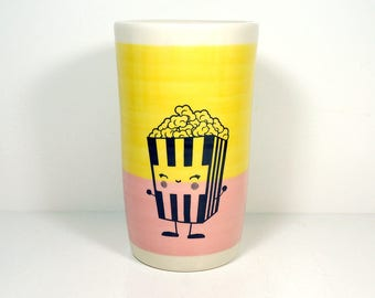 a tall porcelain cylinder/vase/utensil holder with a Happy Popcorn on a colorblock of Lemon Butter & Bubblegum, In Stock / Ready to Ship.