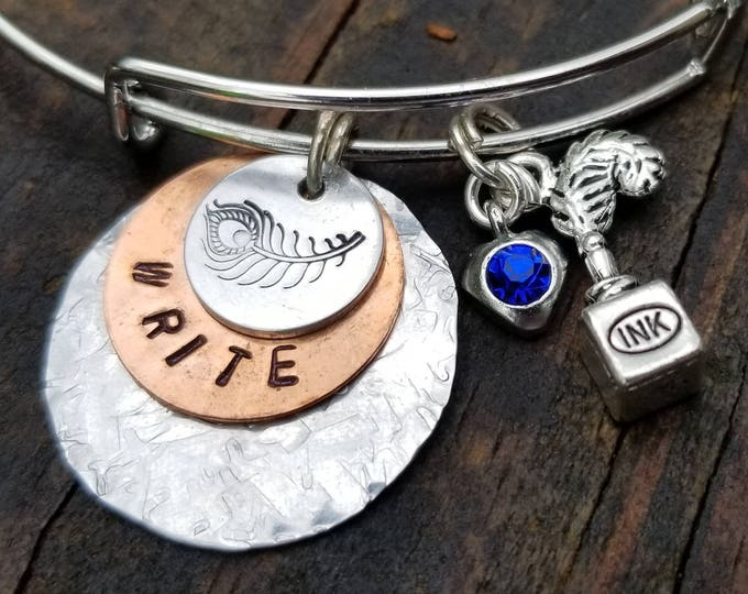WRITE Charm Bangle: Hand-Stamped Aluminum & Copper with Blue Crystal Heart charm and an Ink Quill Charm