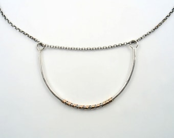 Half Sterling  silver bangle wrapped with solid rose gold strap and held by an oxidized rolo silver chain. Half hoop uniquely  presented.