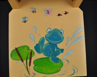 small wooden chair painted peach and painted frog decor