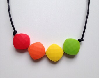Teething necklace in red, orange, yellow, chartreuse green; made from BPA free chewable silicone quadrate beads by Little Gnashers
